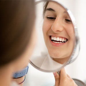 Patient looking at the mirror to see healthy teeth