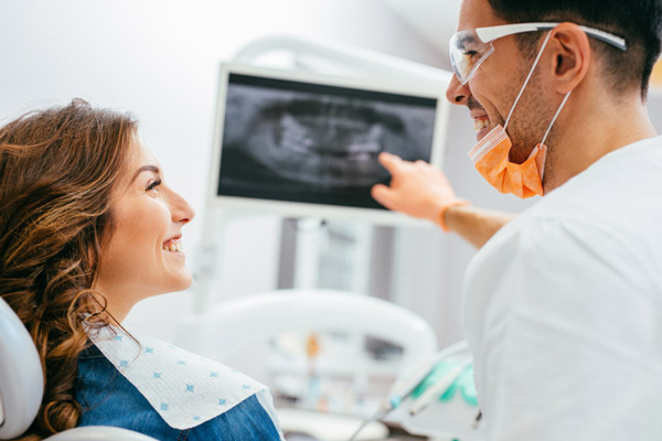 Patient and doctor looking at dental x-ray
