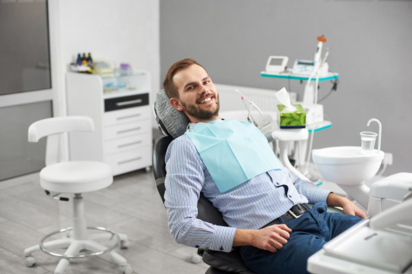 A smiling man in a dental chair