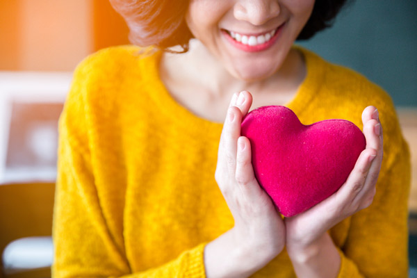 A woman smiling and holding a felt heart